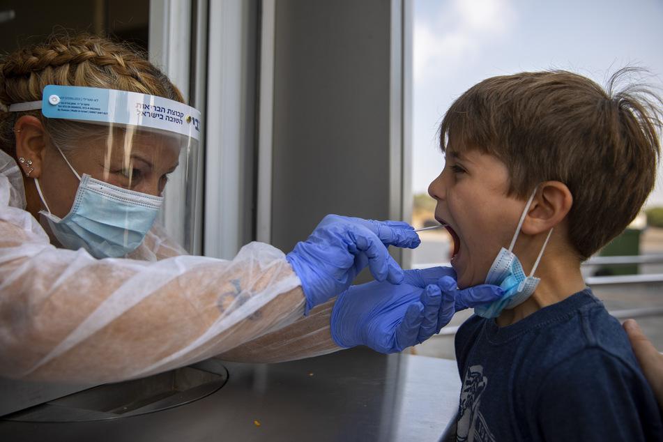 Israel, Tel Aviv: Ein Mitarbeiter des Gesundheitswesens entnimmt einem Kind eine Abstrichprobe, um es in einem Testzentrum auf COVID-19 zu testen.