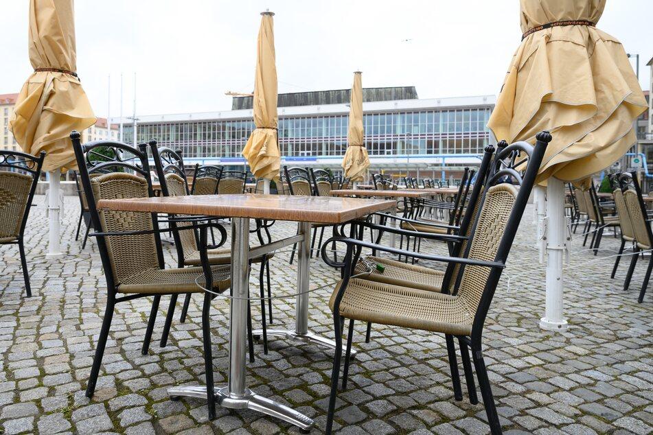 Leere Tische und Stühle stehen vor einem geschlossenen Restaurant auf dem Altmarkt vor dem Kulturpalast.