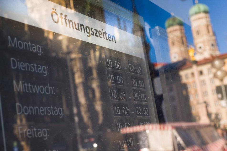 Die Frauenkirche spiegelt sich in einer Schaufensterscheibe in der Münchner Innenstadt, in dem ein Schild mit den Öffnungszeiten eines Landes hängt.