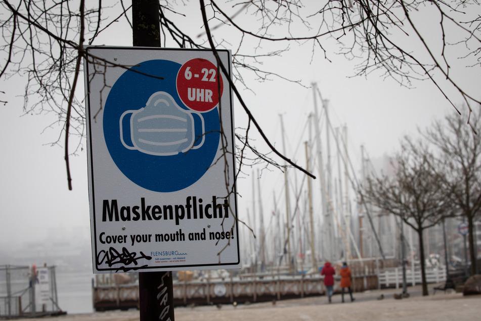 Ein Hinweisschild zur Maskenpflicht ist an der Hafenspitze in der Flensburger Innenstadt zu sehen.