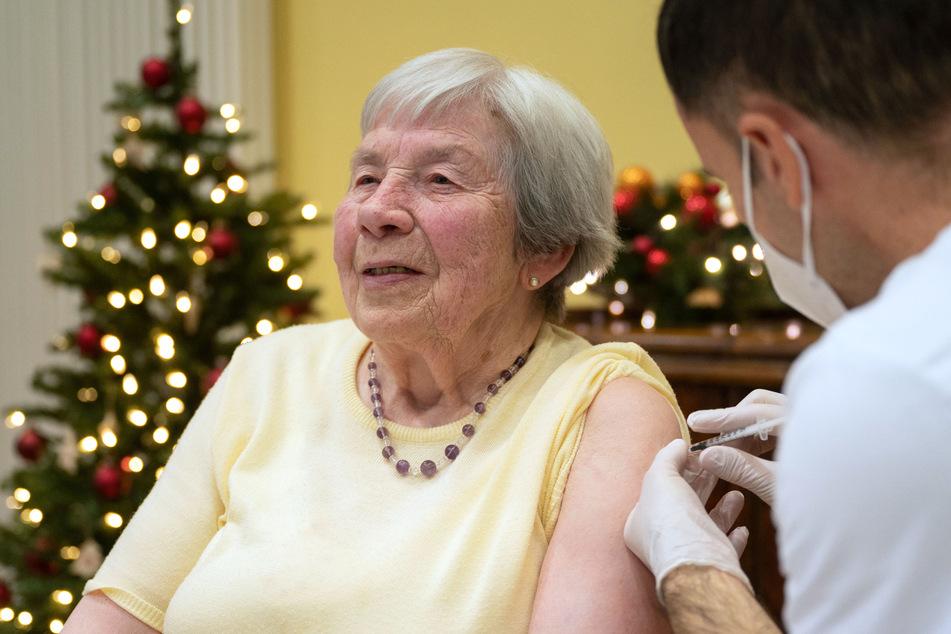 Eine 86 Jahre alte Frau wird in einem Altenpflegeheim von einem Mitglied eines Mobilen Impfteams des Klinikum Stuttgart mit einer Dosis eines Covid-19 Impfstoffes geimpft.