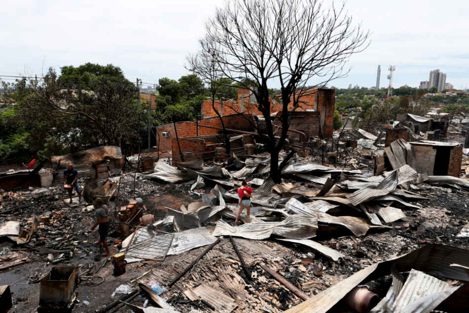 Eine Frau geht mit einem Baby auf ihrem Arm durch die Trümmer.