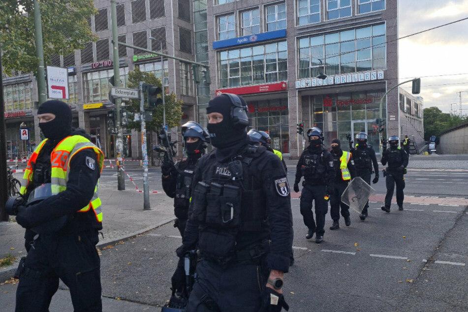 Einsatzkräfte der Polizei gehen am Elcknerplatz am Bahnhof Köpenick Berlin entlang.