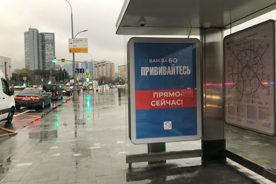 """Moskau wirbt für Corona-Impfungen. An einer Bushaltestelle steht auf dem Plakat: """"Wenn Sie über 60 sind, lassen Sie sich impfen. Gleich jetzt!""""."""