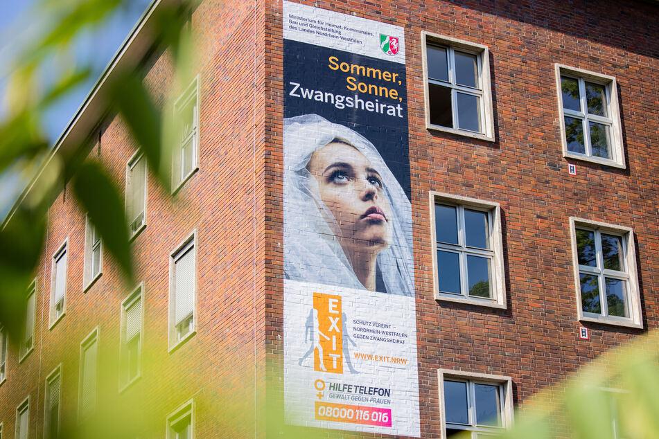 """Ein Plakat mit der Aufschrift """"Sommer, Sonne, Zwangsheirat"""" hängt am Ministerium für Heimat, Kommunales, Bau und Gleichstellung des Landes Nordrhein-Westfalen. Am Dienstag startete eine Kampagne."""
