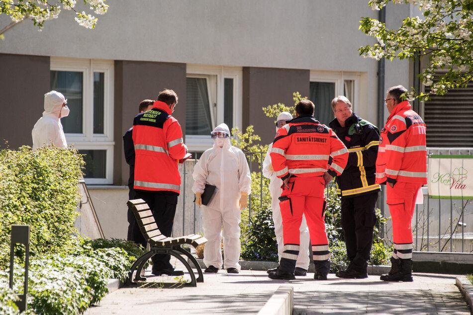 """Einsatzkräfte besprechen sich vor dem Senioren-Zentrum """"Am Inselpark""""."""