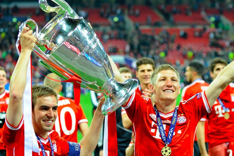 Philipp Lahm (36, l.) und Bastian Schweinsteiger (36, r.) von Bayern München feiern mit dem Pokal nach dem UEFA Champions League-Finale 2013 zwischen Borussia Dortmund und FC Bayern München im Wembley Stadion.