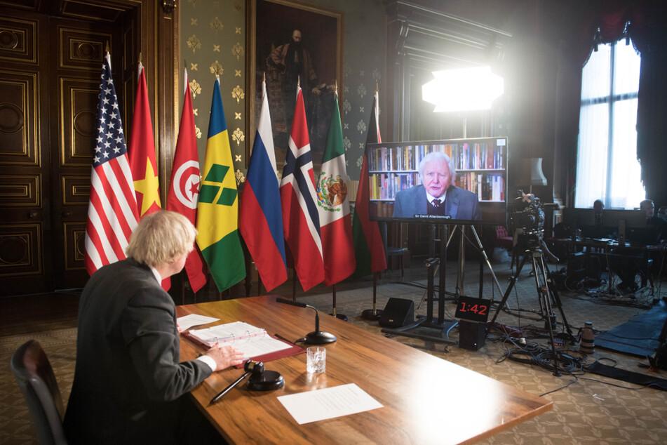 Boris Johnson sieht sich bei einer Sitzung des UN-Sicherheitsrats zum Thema Klima und Sicherheit im Foreign Commonwealth and Development Office eine Videoansprache von Sir David Attenborough an.