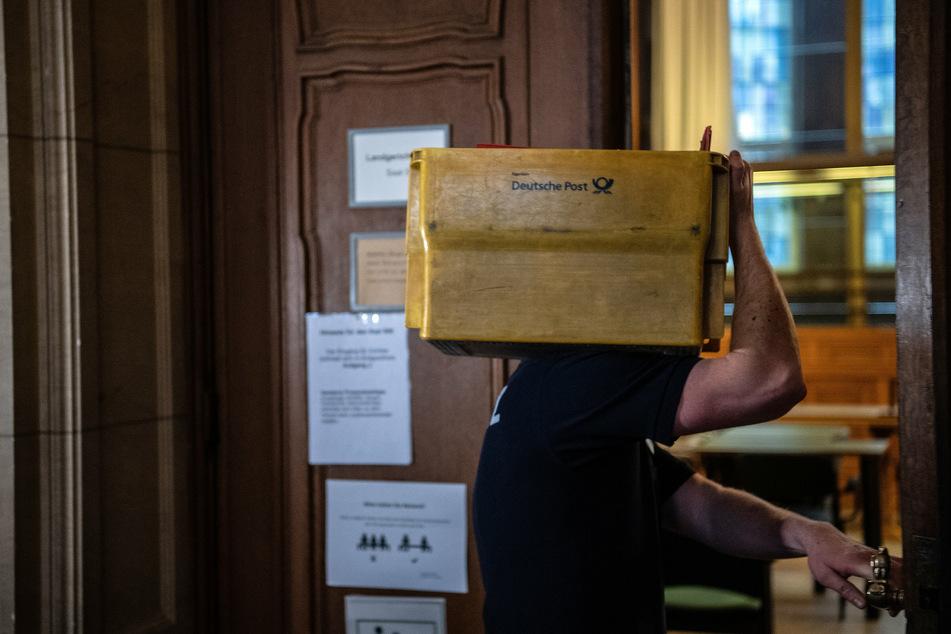 Ein Justizangesteller bringt eine Kiste mit Akten in einen Gerichtssaal.