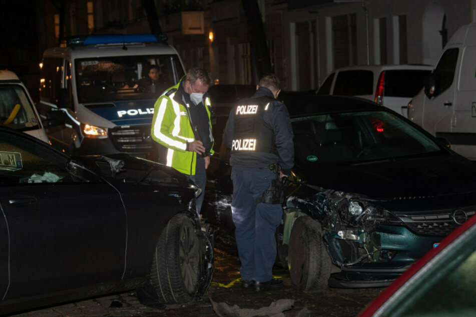 Polizisten betrachten nach der Verfolgungsjagd die beiden Unfallwagen. Bei der Festnahme des 20-jährigen Fahrers soll Polizeigewalt im Spiel gewesen sein.