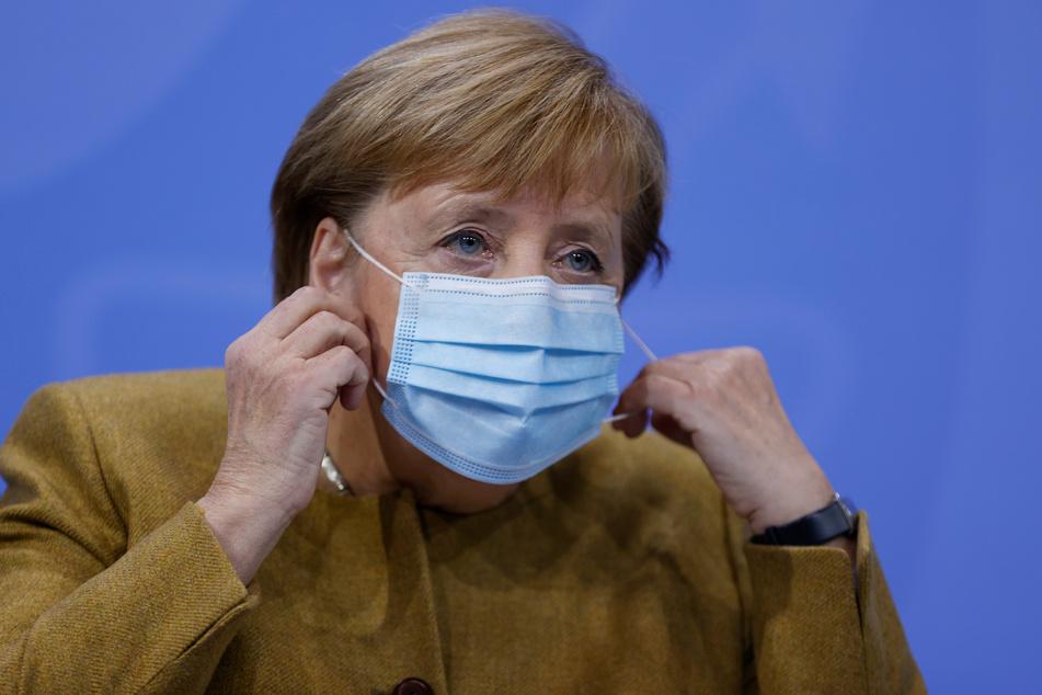 Bundeskanzlerin Angela Merkel (CDU) nimmt ihre Gesichtsmaske vor ihrer Pressekonferenz ab.