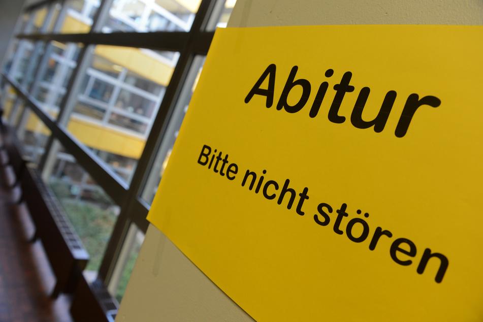 """Ein Blatt mit der Aufschrift """"Abitur - Bitte nicht stören"""" hängt an einem Betonpfosten in einem Gymnasium."""