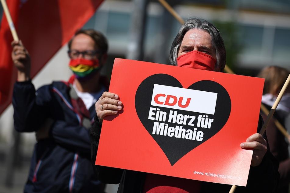 """Ein Demonstrant steht mit einem Plakat mit der Aufschrift """"CDU ein Herz für Miethaie"""" vor der CDU-Bundeszentrale, dem Konrad-Adenauer-Haus."""