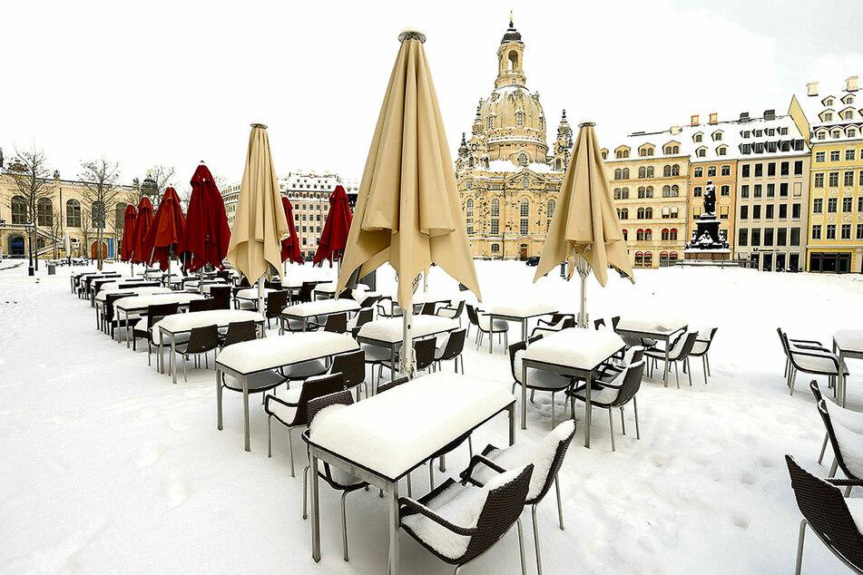 Schlummern auch weiterhin im Lockdown-Winterschlaf unter einer Schneedecke: verwaiste Tische und Stühle auf dem Dresdner Neumarkt an der Frauenkirche.