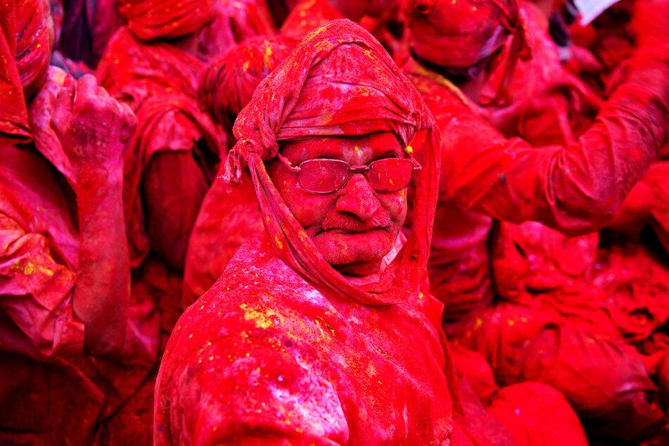 """Ein Hindu ist im indischen Ort Nandgaon mit rotem Farbpulver """"Gulal"""" übersät."""