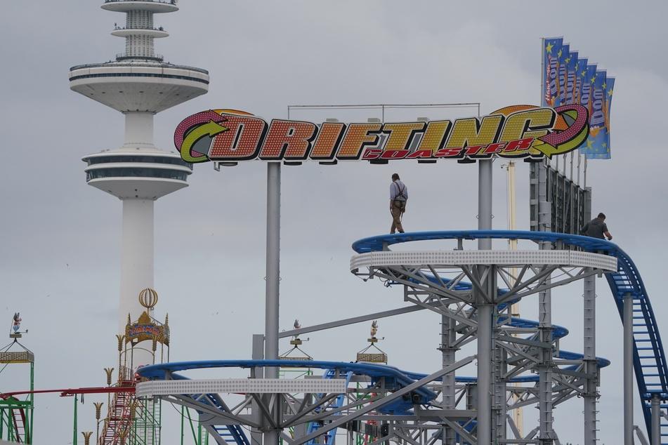 """Mitarbeiter bauen das Fahrgeschäft """"Drifting Coaster"""" auf dem Heiligengeistfeld auf. Der Hamburger Sommerdom findet vom 30. Juli bis 28. August 2021 statt."""
