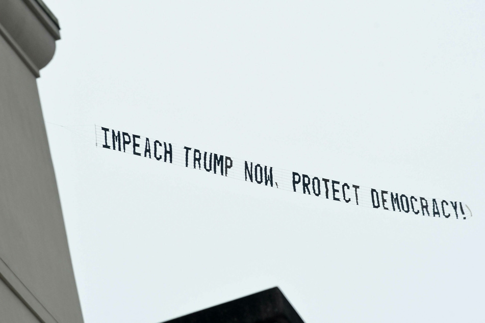 A banner towed by a plane flying in Orlando, Florida, calls for the impeachment of Donald Trump.