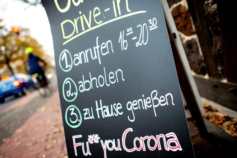"""Eine Tafel mit der Aufschrift """"Drive-in"""" und der Botschaft """"Fu** you Corona"""" steht vor einem geschlossenen Restaurant."""