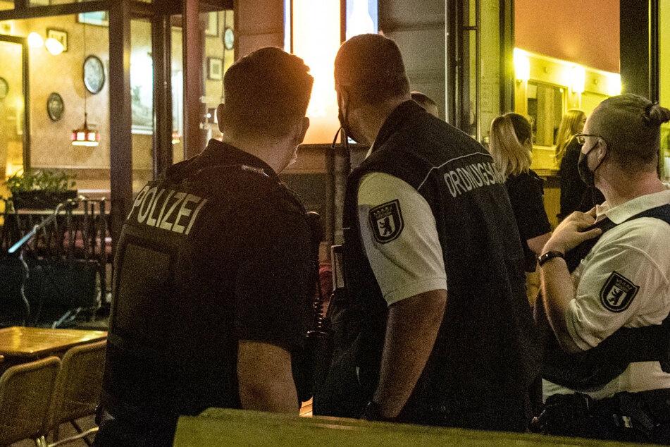 Ein Polizeibeamter und zwei Mitarbeiter des Ordnungsamtes stehen vor einem Lokal in Berlin.