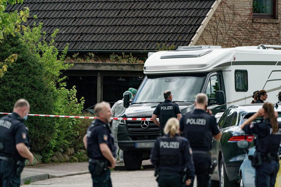 Polizisten untersuchen das Haus, in dem die beiden Toten gefunden wurden.