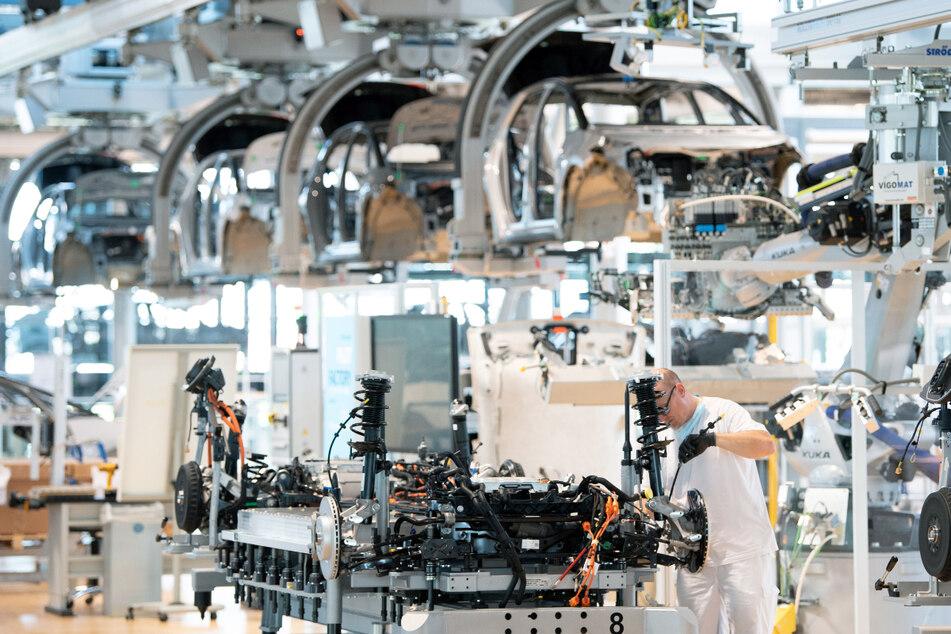 Ein Mitarbeiter arbeitet an der Karosserie eines E-Autos.