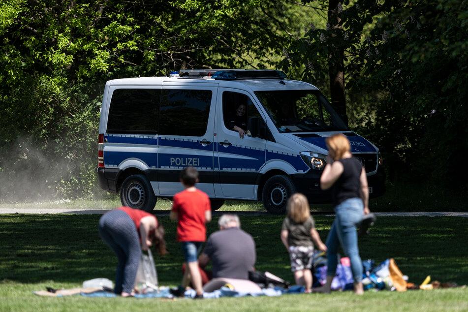 Die Polizei beobachtet kontrolliert in einem Park die Einhaltung der Corona-Schutzmaßnahmen.