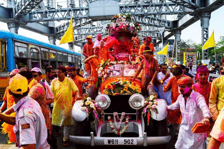 Figuren der Gottheiten Radha und Krishna werden bem Holi-Fest in Kalkutta (Indien) mit einem Auto gefahren.
