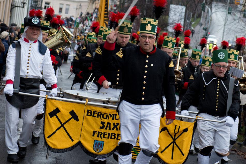 Teilnehmer der Bergparade in Freiberg gehen in historischer Bergarbeiterkleidung durch die Altstadt, das Fest findet auch dieses Jahr wieder statt - trotz Corona.
