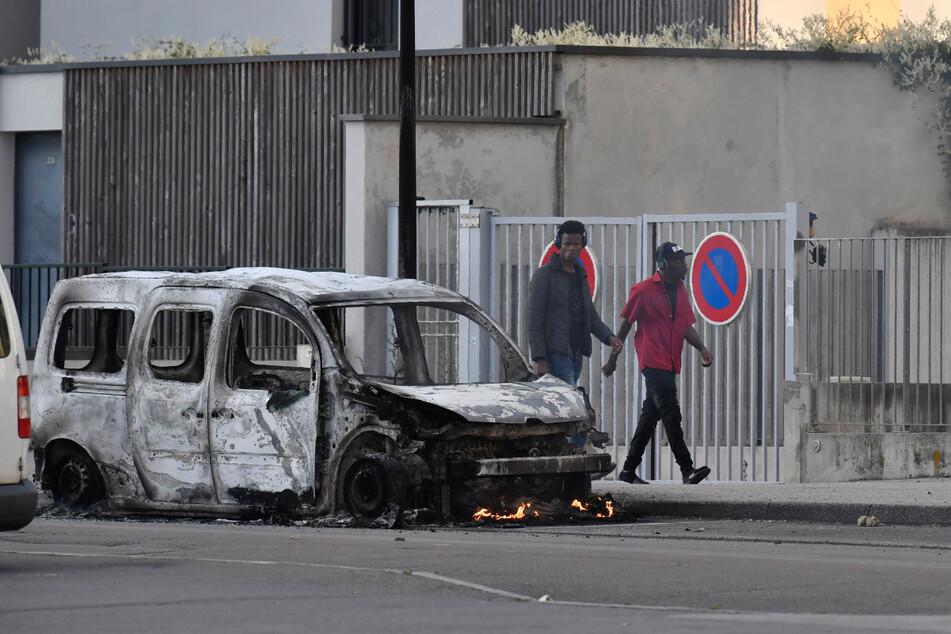 Menschen laufen nach Krawallen im Vorort Gresilles an einem abgebrannten Lieferwagen vorbei.