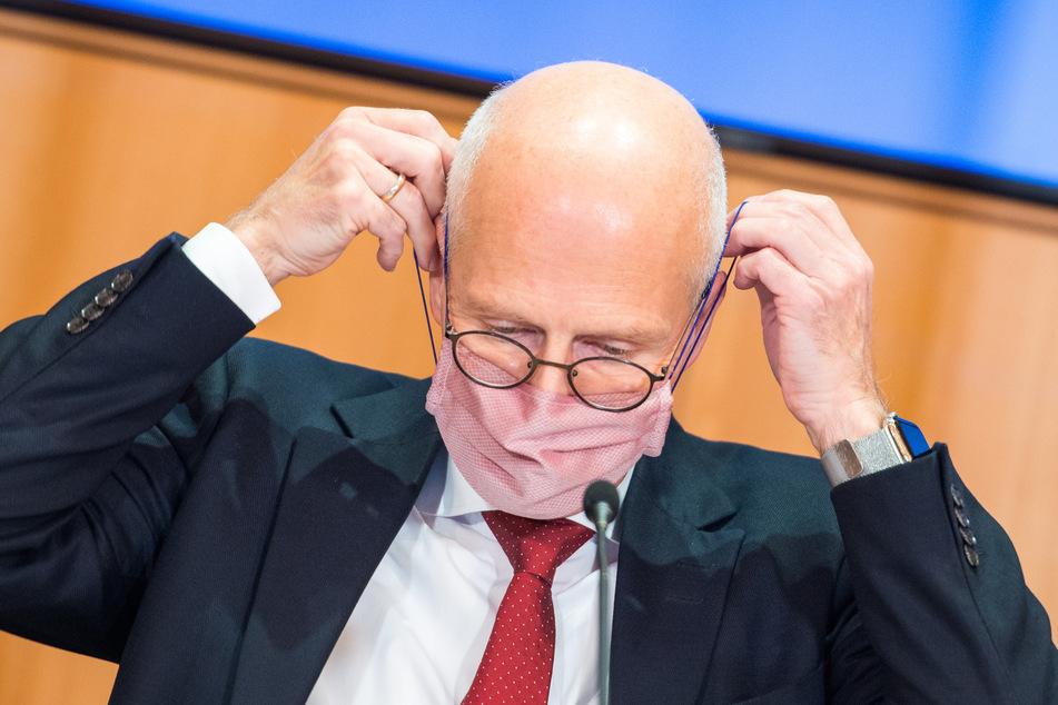 Peter Tschentscher (SPD) setzt sich im Rathaus während einer Pressekonferenz seine Maske (Mund-Nasen-Bedeckung) auf.
