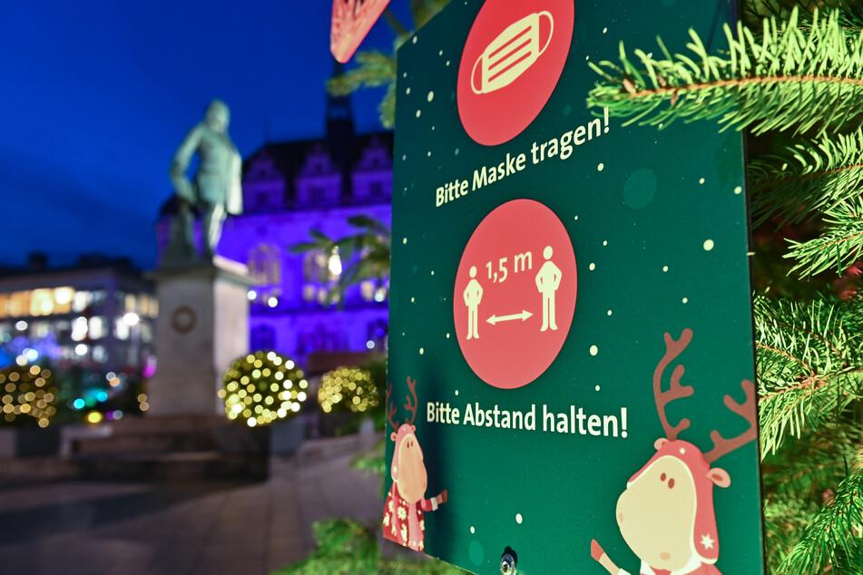 Ein Schild am Markt in Halle/Saale weist auf das Tragen eines Mund-Nasenschutzes und die Einhaltung des Sicherheitsabstandes hin.