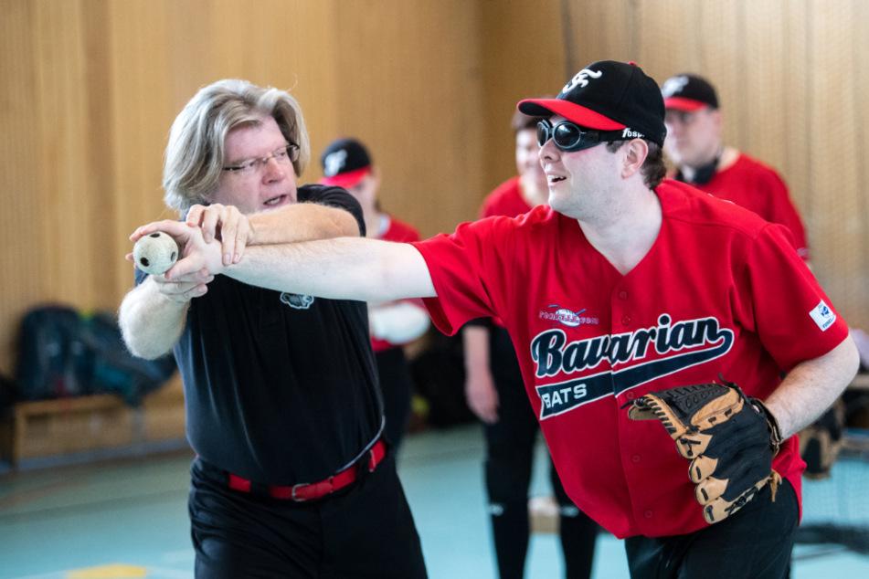 """Hubertus Hagemeyer, Trainer (l), hilft Tobias Geitner, Spieler der Blindenbaseball-Mannschaft """"Bavarian Bats"""", während einer Trainingseinheit bei der Wurftechnik."""