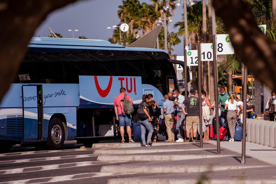 Touristen mit Mundschutz holen ihr Gepäck aus einem Bus des Tourismuskonzerns Tui nahe dem Flughafen Teneriffa.