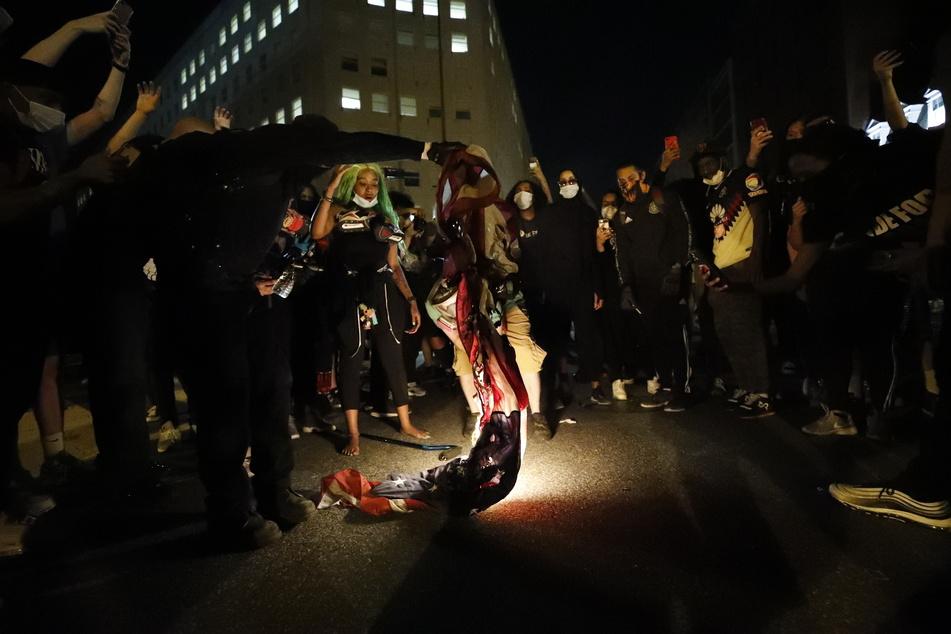 Demonstranten verbrennen während eines Protests in Washington eine amerikanische Flagge.