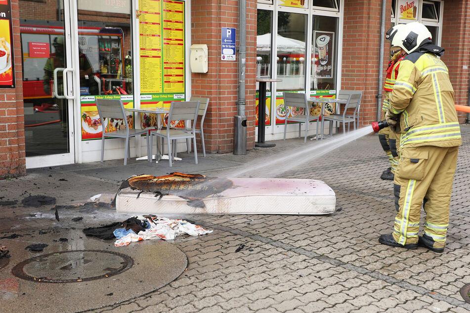 Zigarette trifft Matratze: Feuerwehrleute löschen den Brandherd vor dem Haus.