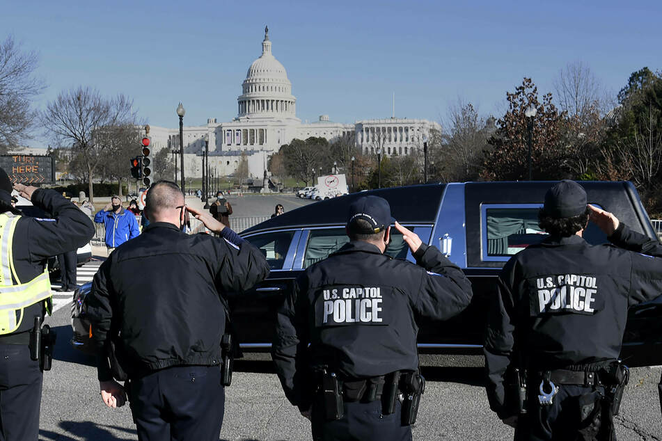 Capitol Hill police salute the passing of the funeral hearse for slain Officer Brian Sicknick, who died in the rioting.