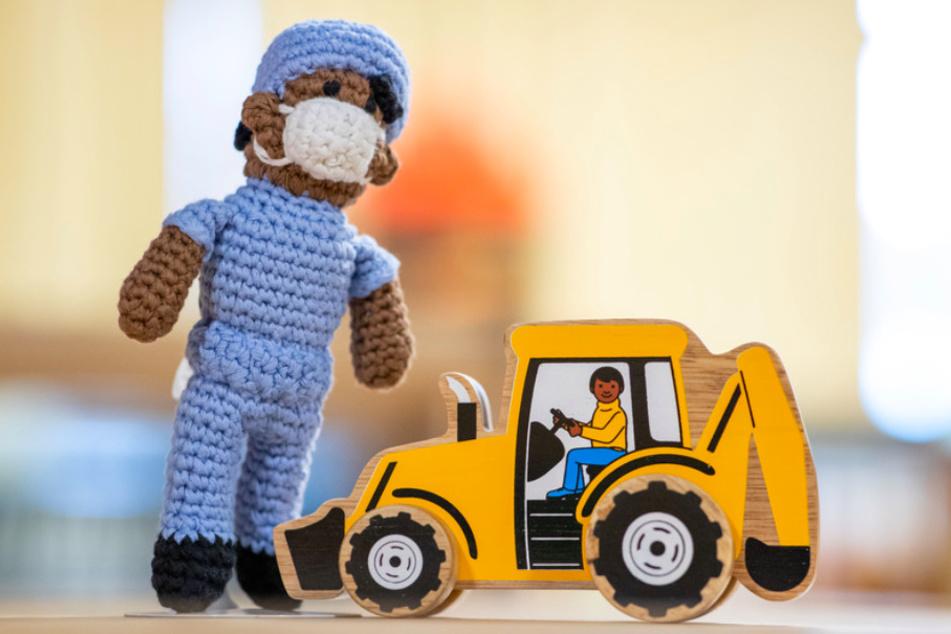 Spielzeug, das nach Aussagen von Mitarbeiterinnen des Museums anti-rassistisch gestaltet sein soll: Eine Puppe, die einen Krankenpfleger darstellen soll, und ein Holzbagger samt Fahrer.