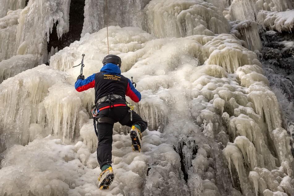 Die richtige Ausrüstung, wie Helm, Sicherheitsgeschirr, Steigeisen und Bergschuhe, ist beim Eisklettern notwendig.