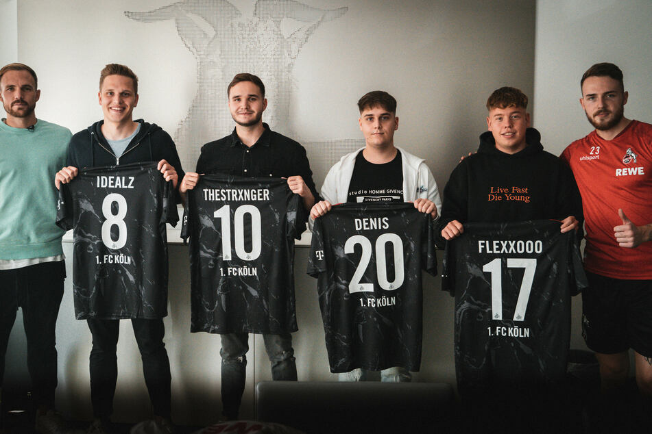 Das neue Team wird von Rafael Czichos (31, l.) und Jannes Horn (24, r.) begrüßt. Die Neuzugänge Lukas Schmandt (25, v.l.n.r.), Tim Katnawatos (22), Denis Müller (19) und Felix Günther (24) halten ihre neuen E-Sport-Trikots in den Händen.