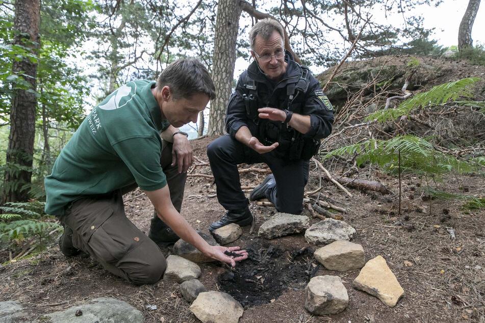Nationalparkleiter Ulf Zimmermann (49, l.) und Erster Polizeihauptkommissar Iven Eißner (51) zeigen die Reste einer illegalen Feuerstätte im Basteigebiet.