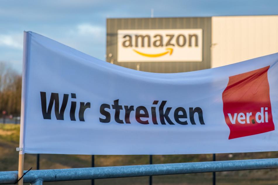 """Das Foto aus dem März dieses Jahres zeigt ein Verdi-Banner mit der Aufschrift: """"Wir streiken"""" vor einem Amazon-Logistik-Zentrum."""