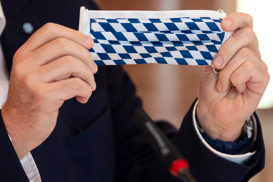 Markus Söder (CSU), Ministerpräsident von Bayern, nimmt an einer Sitzung des bayerischen Kabinetts teil und hält dabei einen Mundschutz mit der bayerische Rautenflagge in den Händen