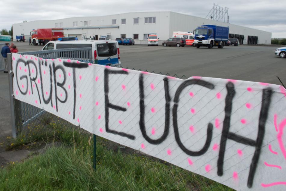 """Ein Banner mit der Aufschrift """"Grüßt euch"""" hängt vor einer Flüchtlingsunterkunft."""