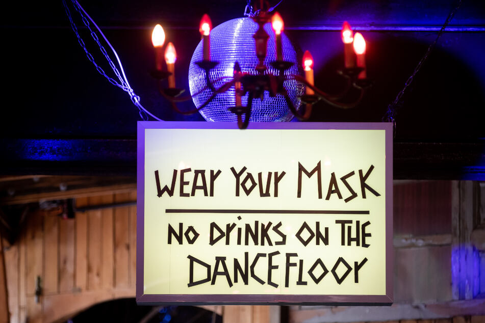 Ein Schild mit der Aufschrift «Wear your mask, no drinks on the dancefloor» (Maske tragen, keine Getränke auf der Tanzfläche) ist am Eingang zum Nachtclub Ritter Butzke in Berlin-Kreuzberg während eines Treffens von Vertretern der Berliner Club-, Kultur- und Veranstaltungsbranche mit Bundesgesundheitsminister Spahn zur Zukunft der Branche zu sehen.