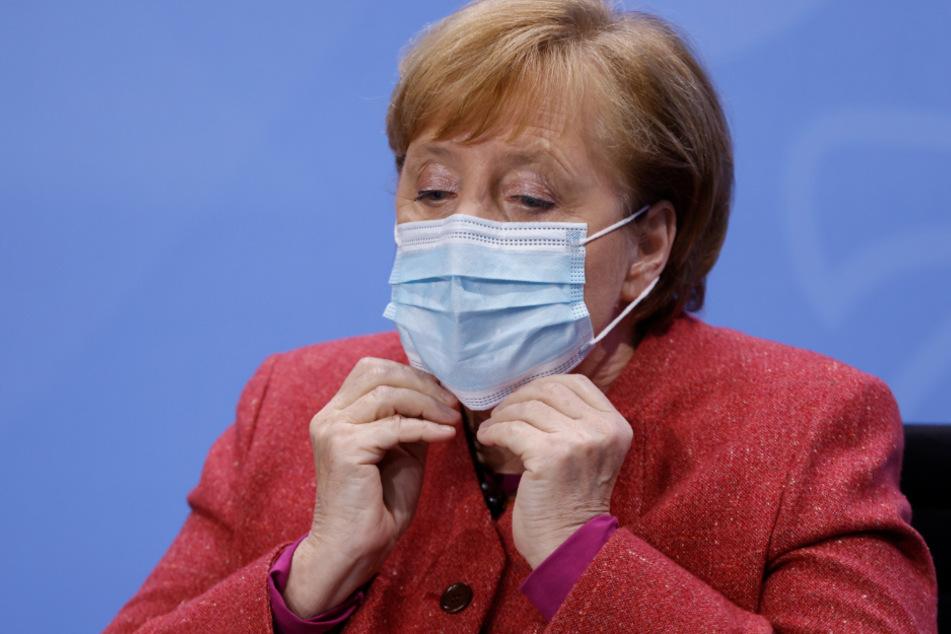 Bundeskanzlerin Angela Merkel setzt sich ihre Mund-Nasen-Bedeckung auf, bevor sie nach einer Pressekonferenz einen Saal im Bundeskanzleramt verlässt.