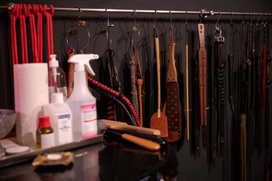 Sexspielzeug und Peitschen hängen in einem Studio hinter Desinfektionsmittel.
