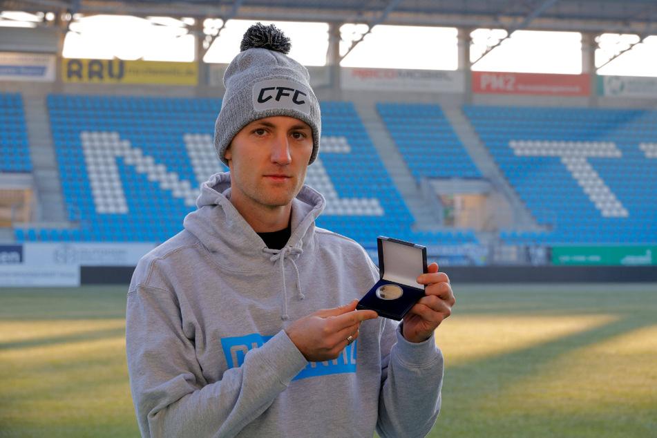 Christian Bickel (29) zeigt stolz seine Goldmedaille, die er für das Tor des Monats Oktober gewann.