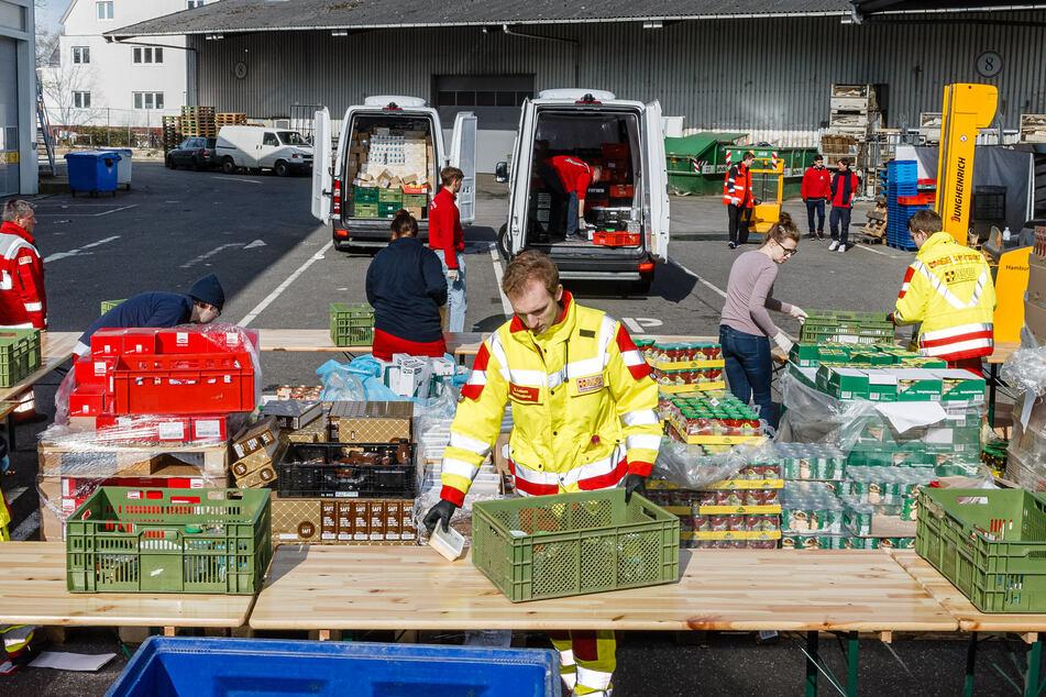 Ehrenamtliche Helfer des Hamburger Tafel und des Arbeiter-Samariter-Bunds packen im Zentraldepot Kisten mit Lebensmitteln.
