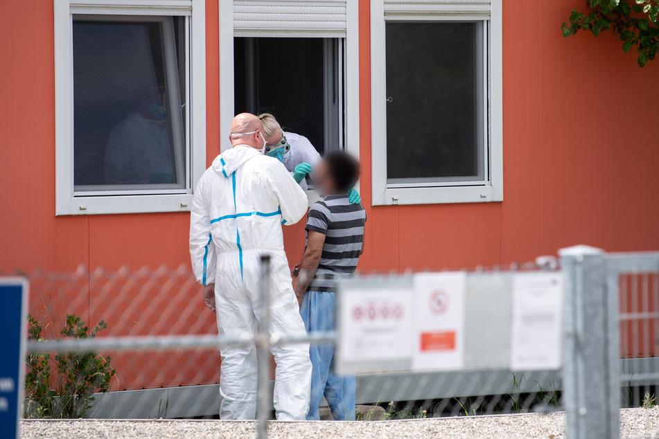 Eine Person im Schutzanzug nimmt an einer Wohncontaineranlage für Flüchtlinge einen Abstrich bei einem Bewohner der Anlage.