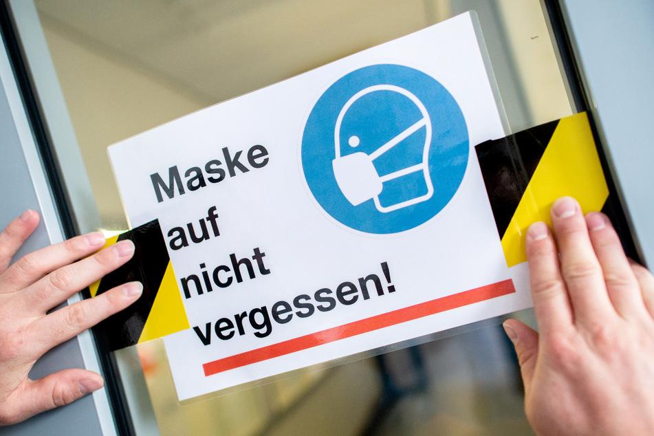 """Der Hausmeister eines Gymnasiums klebt ein Schild mit der Aufschrift """"Maske auf nicht vergessen!"""" an die Glasscheibe einer Zwischentür."""